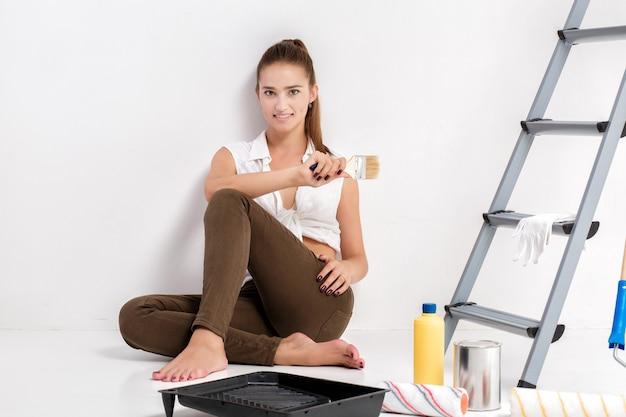 Glimlachende vrouw die muur in haar huis schildert. mooie vrouw met een kwast