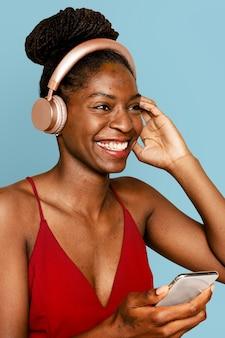 Glimlachende vrouw die muziek streamt met een digitaal smartphoneapparaat
