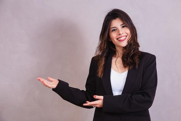 Glimlachende vrouw die naar de kant wijst met vrije ruimte voor tekst.