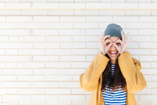 Glimlachende vrouw die ok gebaar zoals verrekijkers doet die jas en gebreide hoed dragen