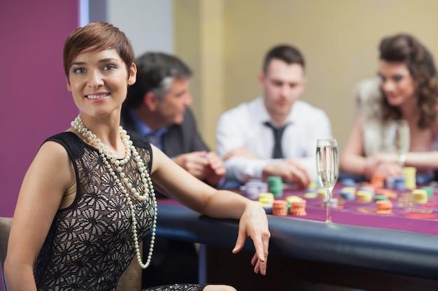 Glimlachende vrouw die onderbreking van roulette met champagne neemt