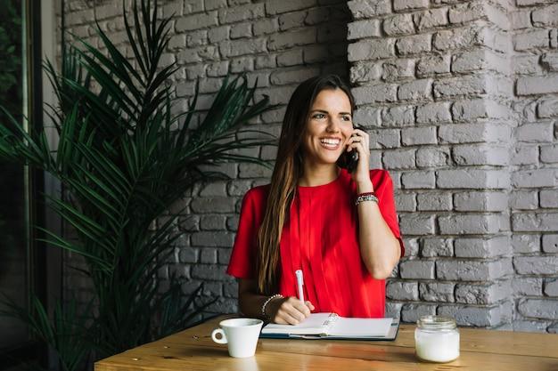 Glimlachende vrouw die op cellphone in cafã� spreekt