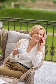 Glimlachende vrouw die op de mobiele telefoon spreekt tijdens haar koffiepauze
