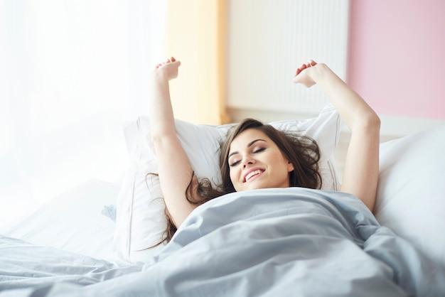 Glimlachende vrouw die op de slaapkamer ligt