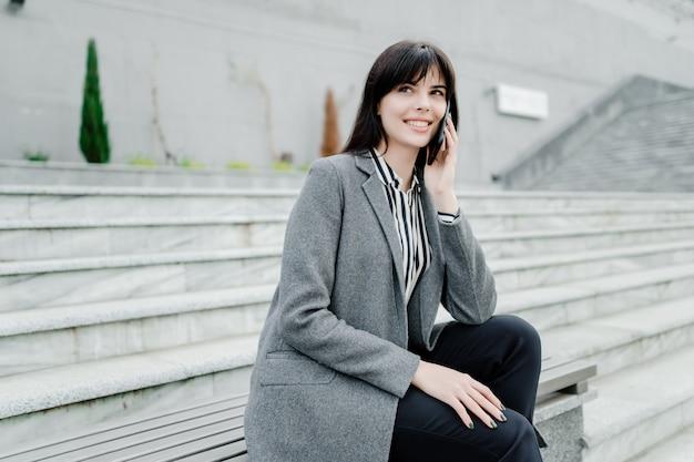 Glimlachende vrouw die op de telefoon in openlucht spreekt