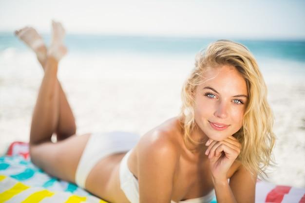 Glimlachende vrouw die op een handdoek bij het strand ligt