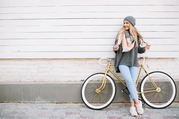 Glimlachende vrouw die op fiets dichtbij muur leunt