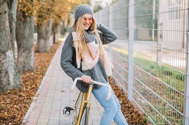 Glimlachende vrouw die op fiets dichtbij omheining leunt