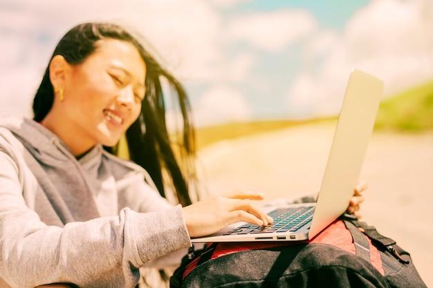 Glimlachende vrouw die op laptop typen die op rugzakken wordt geplaatst