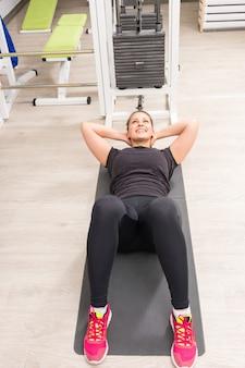 Glimlachende vrouw die op mat bij gymnastiek uitoefent