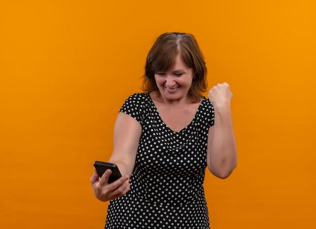 Glimlachende vrouw die op middelbare leeftijd mobiele telefoon met opgeheven vuist op geïsoleerde oranje muur met exemplaarruimte houdt