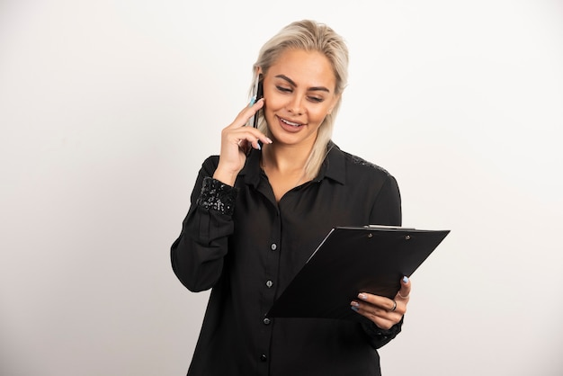 Glimlachende vrouw die op mobiele telefoon spreekt en een klembord houdt. hoge kwaliteit foto