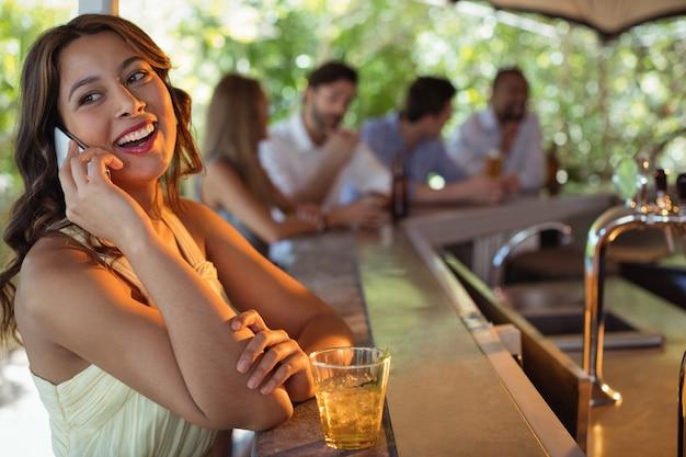 Glimlachende vrouw die op mobiele telefoon spreekt terwijl het hebben van een glas bier in restaurant