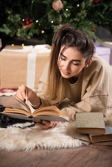 Glimlachende vrouw die op pluizig tapijt ligt en een boek leest.