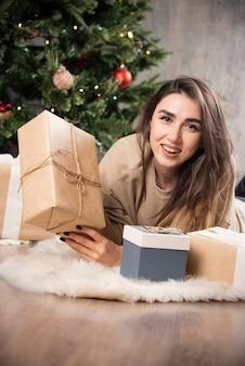 Glimlachende vrouw die op pluizig tapijt ligt en een kerstcadeau toont.