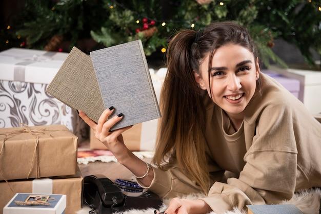Glimlachende vrouw die op pluizig tapijt met boeken ligt.