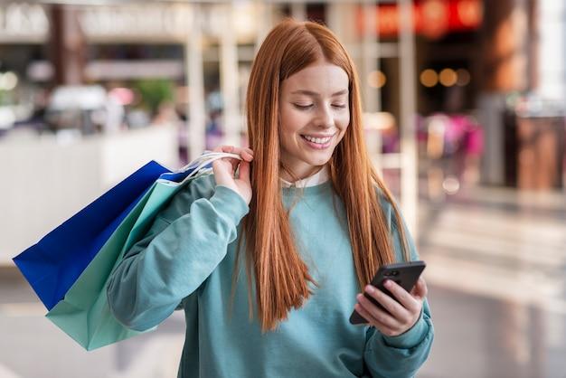 Glimlachende vrouw die op telefoon kijkt