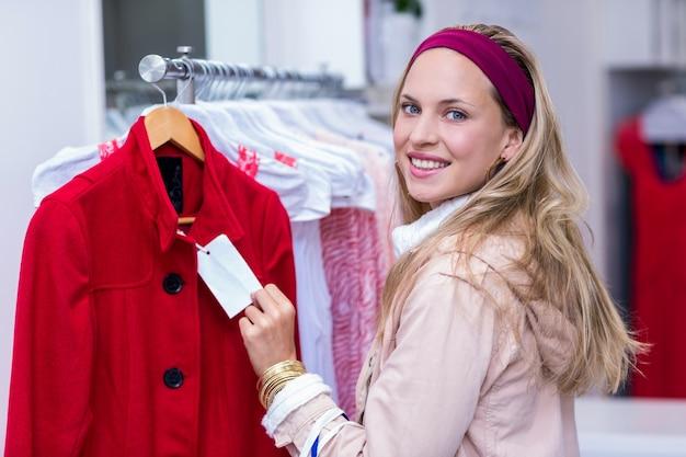 Glimlachende vrouw die prijskaartje toont aan camera