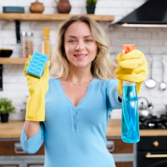 Glimlachende vrouw die rubberhandschoenen draagt die detergens met spons houden