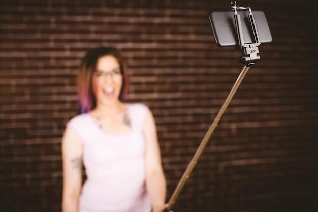 Glimlachende vrouw die selfie van selfiestok nemen