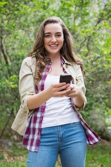 Glimlachende vrouw die smartphone gebruikt