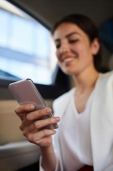 Glimlachende vrouw die smartphone in auto gebruiken