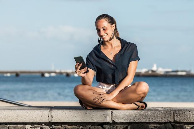 Glimlachende vrouw die smartphone op dijk in de zomer gebruikt