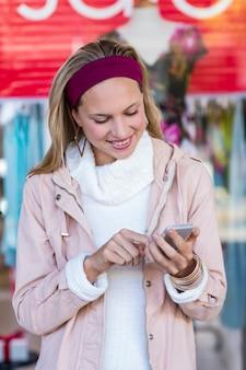 Glimlachende vrouw die smartphone voor venster gebruiken