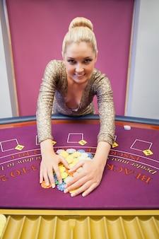 Glimlachende vrouw die spaanders in een casino grijpen