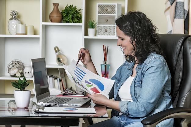 Glimlachende vrouw die statistiek in rapporten analyseert terwijl het werken bij laptop in lichte moderne flat
