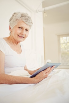 Glimlachende vrouw die tabletzitting op het bed gebruikt
