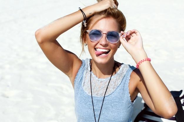 Glimlachende vrouw die tong en zittend op het strand