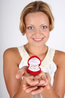 Glimlachende vrouw die trouwringen in rode doos houdt. focus op ringen