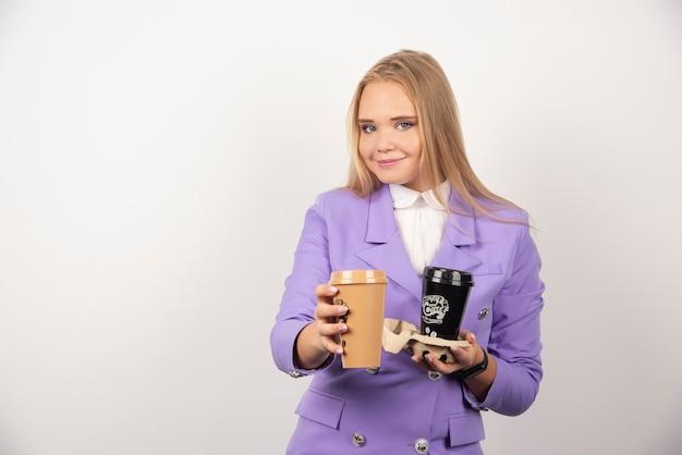 Glimlachende vrouw die twee kopjes koffie op wit aanbiedt