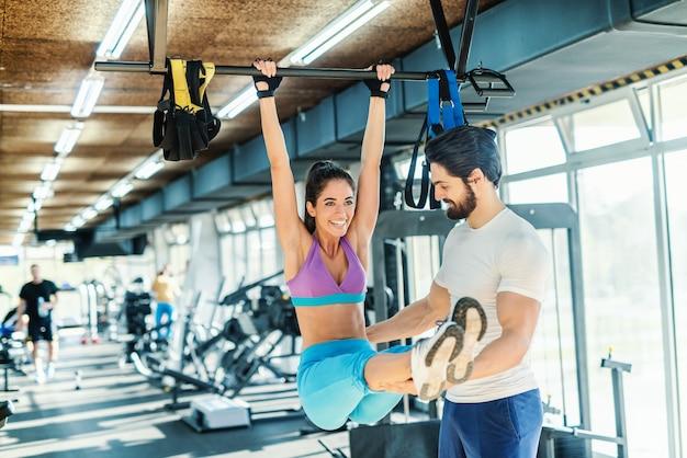 Glimlachende vrouw die uithoudingsvermogen op staaf doet terwijl haar persoonlijke trainer haar helpt. gym interieur.