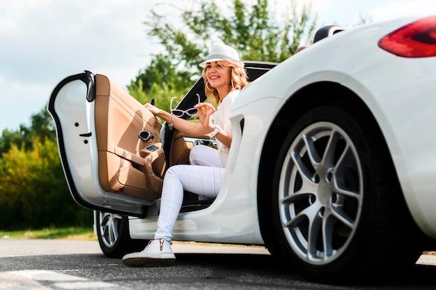 Glimlachende vrouw die van auto weggaat