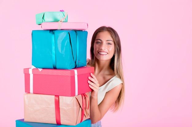 Glimlachende vrouw die van de stapel kleurrijke giftdozen gluren tegen roze achtergrond