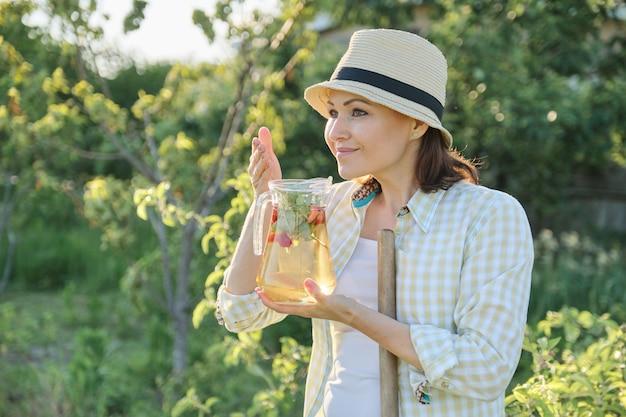 Glimlachende vrouw die van het aroma van verse eigengemaakte kruidendrank geniet