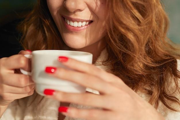 Glimlachende vrouw die van koffie in de ochtend geniet