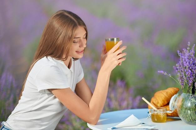 Glimlachende vrouw die van maaltijd op lavendelgebied geniet