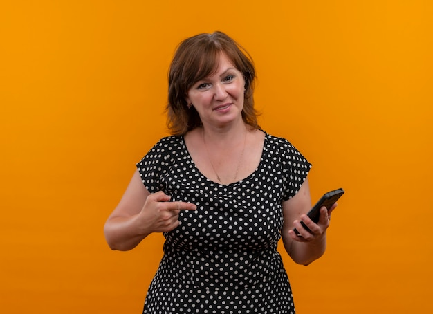 Glimlachende vrouw die van middelbare leeftijd mobiele telefoon houdt en met vinger erop richt op geïsoleerde oranje muur met exemplaarruimte