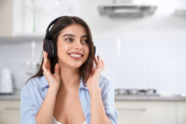 Glimlachende vrouw die van mooie muziek in hoofdtelefoon geniet