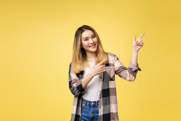 Glimlachende vrouw die vingerkant richt. geïsoleerde portret op geel.