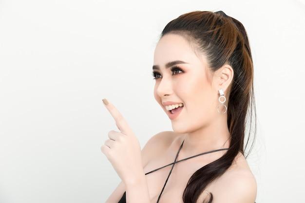 Glimlachende vrouw die vingerkant richt. geïsoleerde portret op wit