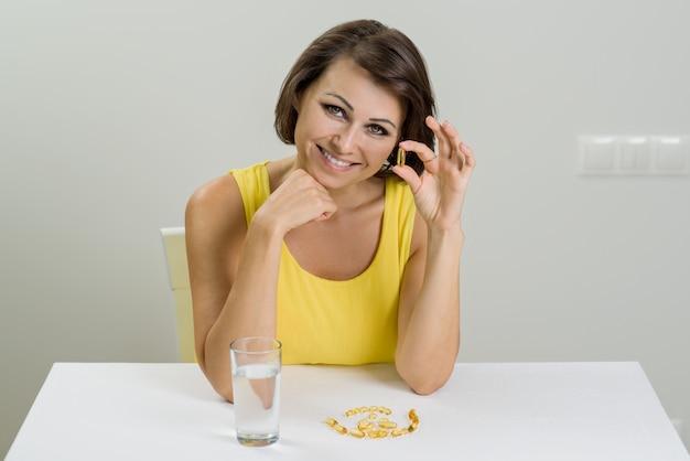 Glimlachende vrouw die visoliepil omega-3 nemen. vitamine d, e, a visolie capsules