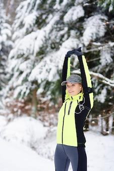Glimlachende vrouw die vóór hardlopen opwarmt
