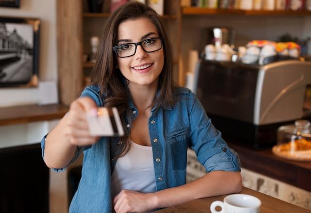 Glimlachende vrouw die voor koffie met creditcard betaalt