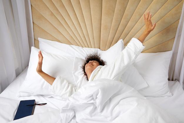 Glimlachende vrouw die wakker wordt in bed en haar armen uitstrekt