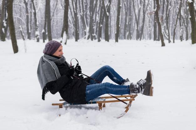 Glimlachende vrouw die warme kleren dragen die op slee over het sneeuwlandschap zitten