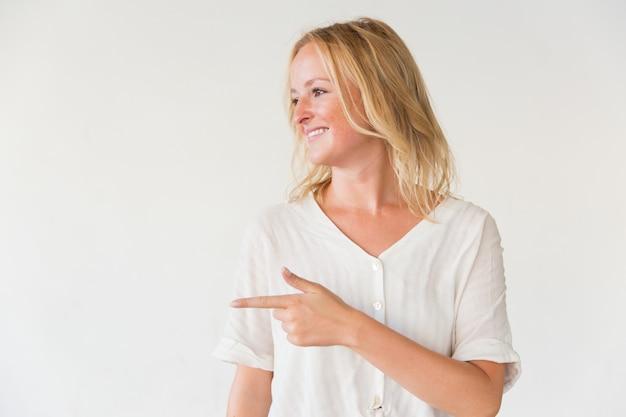 Glimlachende vrouw die weg met vinger richt